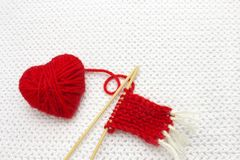 Czerwona przędzy piłka jak serce na białym szydełkowym tle Romantyczny walentynka dnia pojęcie Czerwony serce robić wełny przędza Zdjęcie Royalty Free