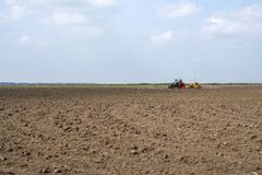 Czerwona rolnego ciągnika narządzania ziemia dla siać obrazy stock