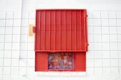Czerwona siatki żaluzja na biel ścianie fotografia royalty free