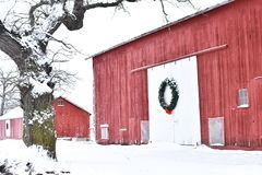 Czerwona stajnia w zimie z Bożenarodzeniowym wiankiem fotografia stock