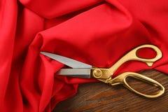 Czerwona tkanina i ostrzy nożyce na drewnianym stole zdjęcia royalty free