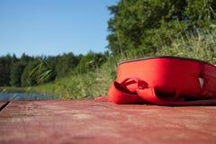 Czerwona torba kłaść na brown drewnianych deskach przeciw niebieskiemu niebu, woda, zieleni płochy i las i zdjęcie royalty free