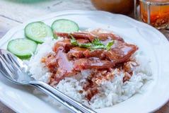 Czerwona wieprzowina z ryż i ogórkiem na talerzu fotografia stock