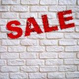 Czerwona wpisowa sprzedaż na ściana z cegieł bielu z skutkiem podława farba, Zdjęcia Stock
