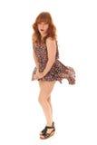 Czerwona z włosami dziewczyny pozycja w wiatrze odizolowywającym nad białym tłem Obraz Royalty Free