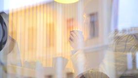 Czerwona z włosami imbirowa kobieta używa pecet pastylki komputerowego ekran sensorowego w kawiarni pije kawę zbiory