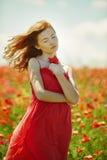 Czerwona z włosami piękna dziewczyna w maczka polu Obraz Royalty Free