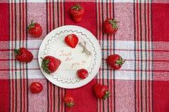 Czerwone Świeże truskawki na Ceramicznym bielu talerzu na czeku T Obrazy Royalty Free