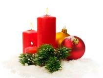Czerwone świeczki, jodeł gałąź i Bożenarodzeniowe piłki w śniegu Fotografia Stock