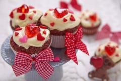 Czerwone aksamitne babeczki dekorować z sercami obrazy stock