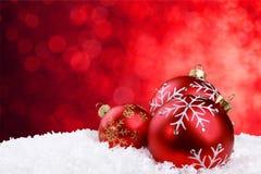 Czerwone błyszczące boże narodzenie piłki w płatkach śniegu Fotografia Royalty Free