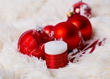 Czerwone boże narodzenie piłki i dekorująca świeczka na futerkowym tle Zdjęcia Stock