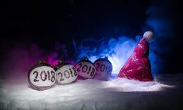 Czerwone boże narodzenie piłki z 2018 liczb i Santa klauzula kapeluszem na naturalnym śnieżnym tle Szczęśliwy nowego roku 2018 po Obrazy Stock