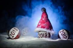 Czerwone boże narodzenie piłki z 2018 liczb i Santa klauzula kapeluszem na naturalnym śnieżnym tle Szczęśliwy nowego roku 2018 po Zdjęcie Royalty Free