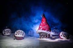 Czerwone boże narodzenie piłki z 2018 liczb i Santa klauzula kapeluszem na naturalnym śnieżnym tle Szczęśliwy nowego roku 2018 po Zdjęcia Royalty Free