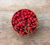 Czerwone dojrzałe wiśnie z ogonami w kurenda talerzu na starym drewnianym tle obraz royalty free