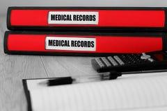Czerwone falcówki z książeczkami zdrowia pisać na etykietce na biurku obraz stock
