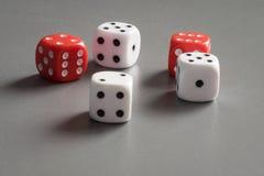 Czerwone i białe kostki do gry na zmroku siwieją tło zdjęcia stock