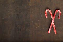 Czerwone i białe cukierek trzciny na drewnianym tle Obrazy Stock