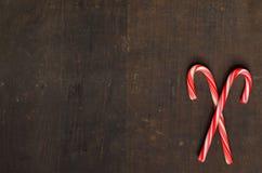 Czerwone i białe cukierek trzciny na drewnianym tle Fotografia Stock