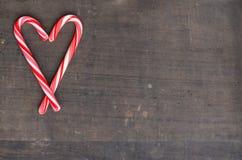 Czerwone i białe cukierek trzciny w sercu na drewnianym tle Zdjęcie Royalty Free