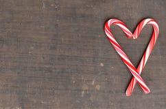 Czerwone i białe cukierek trzciny w sercu na drewnianym tle Obrazy Royalty Free