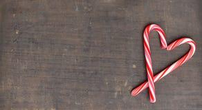 Czerwone i białe cukierek trzciny w sercu na drewnianym tle Obrazy Stock
