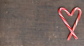 Czerwone i białe cukierek trzciny w sercu na drewnianym tle Zdjęcia Royalty Free