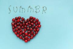 Czerwone jagodowe wiśnie w kształcie serca i teksta lato życie na błękitnym tle, Wciąż Mieszkanie nieatutowy, odgórny widok Odbit obraz stock