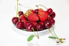 czerwone jagody truskawki i Burgundy wiśnie z liśćmi na talerzu odizolowywającym na białym tle obrazy stock