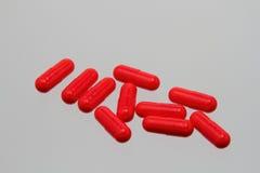 Czerwone kapsuły na białym tle Fotografia Royalty Free