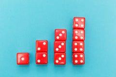 Czerwone kostki do gry w postaci wykresu, wzrasta jeden, cztery od, na błękitnym tle obrazy stock