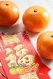 Czerwone paczki i mandarynek pomarańcze, złoty chińczyka list znaczą lu Obraz Stock