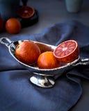 Czerwone pomarańcze w metal wazie zdjęcie stock