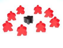 Czerwone postacie otaczają czarną postać zdjęcie royalty free