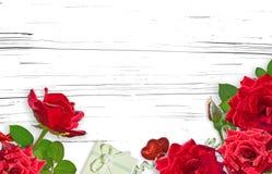 Czerwone róże i prezent na białym drewnianym tle kwiat rama Obraz Stock