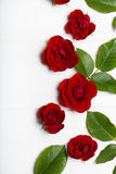 Czerwone róże i zieleń liście na białym drewnianym stole Rocznik Flor obrazy royalty free