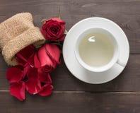 Czerwone róże kwitną i filiżanka herbata jest na drewnianym tle Zdjęcie Royalty Free