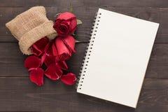Czerwone róże kwitną i notatnik jest na drewnianym tle Obrazy Stock