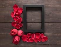 Czerwone róże kwitną i ramowy obrazek jest na drewnianym backgrou Zdjęcia Stock