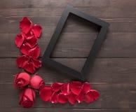 Czerwone róże kwitną i ramowy obrazek jest na drewnianym backgrou Obrazy Stock