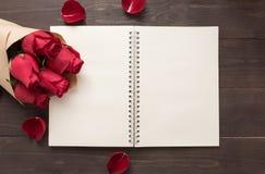 Czerwone róże kwitną z notatnikiem są na drewnianym tle Zdjęcia Stock