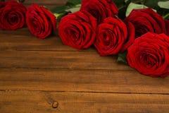 Czerwone róże na drewnianym stole Fotografia Stock