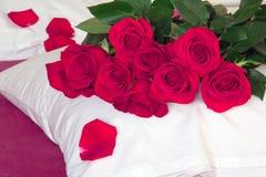 Czerwone róże na poduszce i czerwieni prześcieradłach Zdjęcia Royalty Free