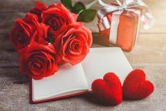 Czerwone róże, pudełko na drewnianym backgrou, czerwony serca, notatnika i prezenta, Obraz Stock