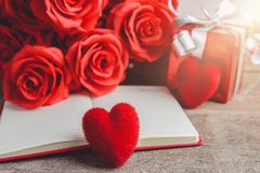 Czerwone róże, pudełko na drewnianym backgrou, czerwony serca, notatnika i prezenta, Zdjęcie Royalty Free