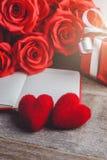 Czerwone róże, pudełko na drewnianym backgrou, czerwony serca, notatnika i prezenta, Zdjęcia Stock