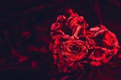 Czerwone róże w kierowym kształcie na jedwabniczym tle fotografia stock