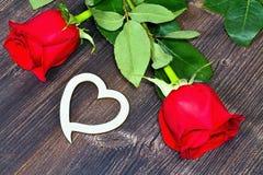 Czerwone róże z drewnianym sercem Dla kochanków Róże, serce, opuszczają na drewnianym stole Zdjęcia Stock
