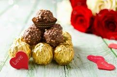 Czerwone róże, serca i cukierek na drewnianym tle, Fotografia Stock